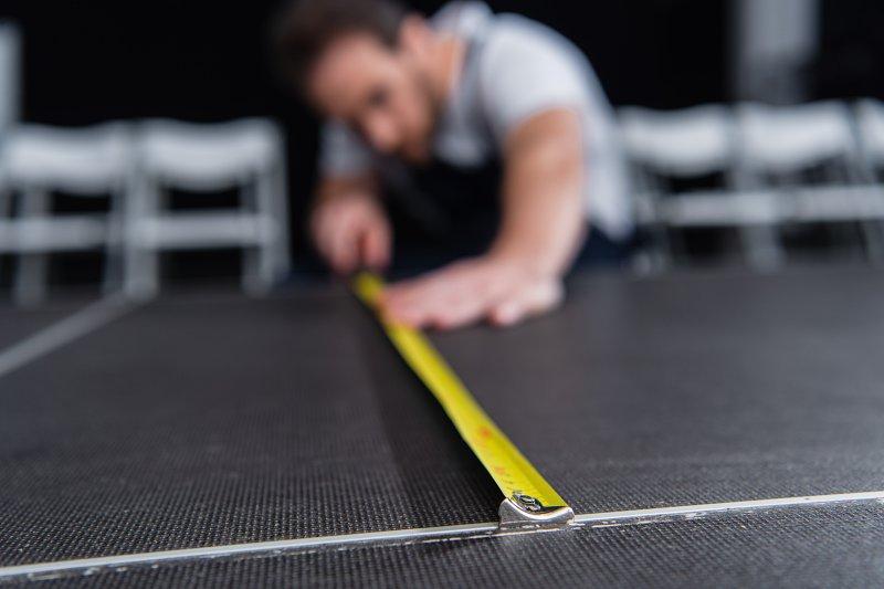 Měření podlahy svinovacím metrem.