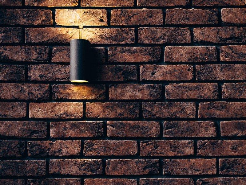 Přiznaná zeď z cihel s lampičkou.