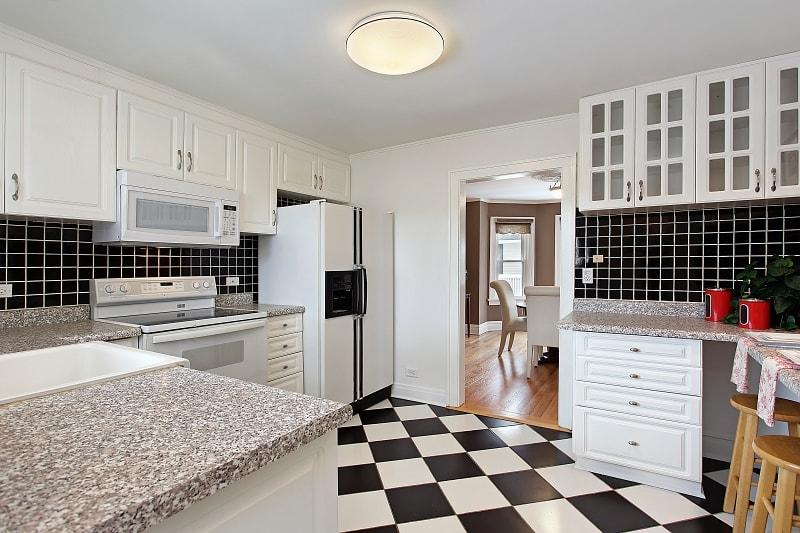 Černo bílé kostky na podlaze v kuchyni položené na koso.